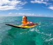 Beautiful young blonde woman in a bright bikini surfing in Mauritius in the Indian Ocean on the background of blue sky, clouds and transparent waves
